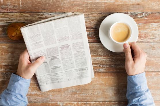 man met krant en koffie